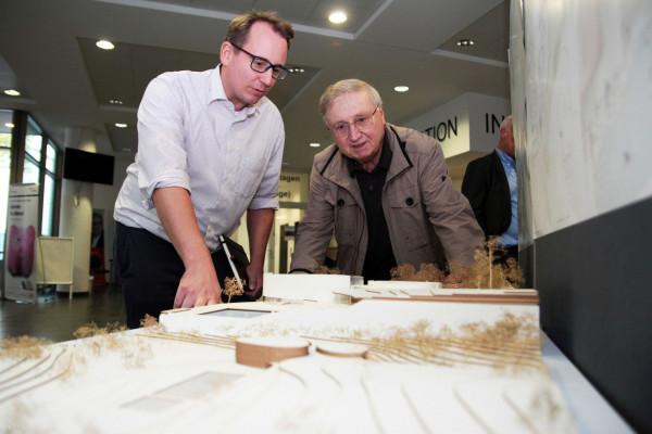 Die SPD-Ratsmitglieder Burkart Jentsch (li.) und Dieter Fleskes schauen sich die Entwürfe der Architektur-Studierenden zum Hallenfreibad Höntrop an.