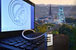 Symbolbild: Laptop mit Logo und Datenkabel in einem Vorhängeschloss als Illustration eines geplanten Instituts für Cybersicherheit der Max-Planck-Gesellschaft in Bochum