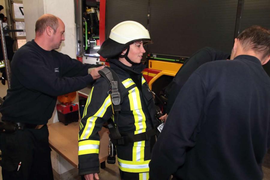 Feuerwehrbeamte helfen Deborah Steffens dabei, die schwere Ausrüstung samt Sauerstoffmaske abzulegen.