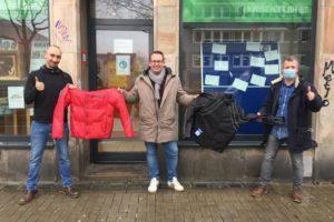 Tobias Fechner von der Krisenhilfe (l.) nimmt die Winterkleidung von Jörg Laftsidis und Burkart Jentsch (m.) entgegen.